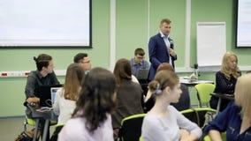 De groep studenten in klaslokaal bij de universiteit is aandachtig luisterend de lezing op Economie van beroemde spreker stock videobeelden