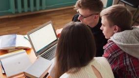 De groep studenten leert samen en bekijkt laptop het scherm stock footage
