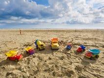 De groep stuk speelgoed werkende vrachtwagens van verschillende grootte en kleuren schikte in een halve cirkel op het strand Stock Afbeeldingen