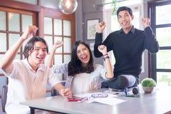 De groep succesvolle freelancers viert het werken van samen het zitten stock fotografie