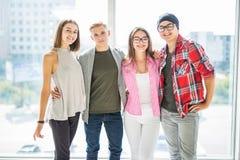De groep tieners en meisjes bekijkt camera, koestert en glimlacht terwijl binnen status stock foto's