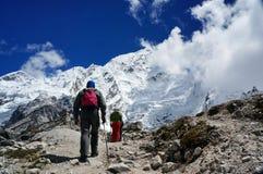 De groep toeristen beklimt de sleep op de achtergrond van de snow-covered Himalayan-bergen Stock Foto's