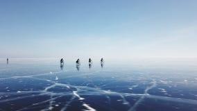De groep toeristen berijdt fietsen op het ijs van Baikal Het schieten met een quadrocopterhommel Ijs van het bevroren Meer stock footage