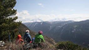 De groep toeristen zit bij de bovenkant van de heuvel en neemt montains met sneeuwpieken waar stock footage
