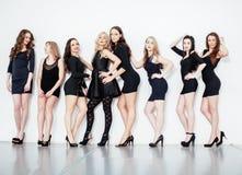 De groep velen koelt moderne meisjesvrienden in de diverse zwarte kleding die van de manierstijl samen die pret hebben op wit wor Royalty-vrije Stock Foto