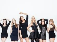 De groep velen koelt moderne meisjesvrienden in de diverse zwarte kleding die van de manierstijl samen die pret hebben op wit wor Royalty-vrije Stock Foto's