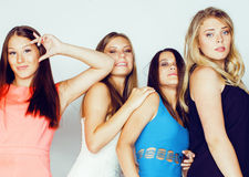 De groep velen koelt moderne meisjesvrienden die in die heldere clothers samen pret hebben op witte gelukkige achtergrond wordt g Stock Foto