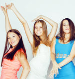 De groep velen koelt moderne meisjesvrienden die in die heldere clothers samen pret hebben op witte gelukkige achtergrond wordt g Stock Foto's