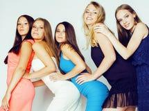 De groep velen koelt moderne meisjesvrienden die in die heldere clothers samen pret hebben op witte gelukkige achtergrond wordt g Stock Afbeelding
