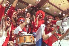 De groep ventilators kleedde zich in rode kleur lettend op een sportengebeurtenis Stock Afbeelding