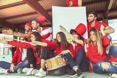 De groep ventilators kleedde zich in rode kleur lettend op een sportengebeurtenis Royalty-vrije Stock Fotografie