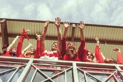 De groep ventilators kleedde zich in rode kleur lettend op een sportengebeurtenis Stock Foto's