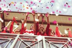 De groep ventilators kleedde zich in rode kleur lettend op een sportengebeurtenis Royalty-vrije Stock Foto