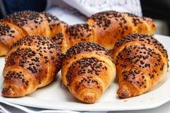 De groep vers gebakken die croissants met chocoladeschilfers worden verfraaid ligt op een witte plaat royalty-vrije stock fotografie
