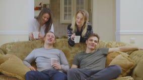 De groep vrienden deelt thuis en drinkt koffie mee stock videobeelden