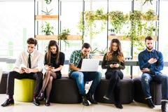 De groep vrienden die op stoelen dichtbij elkaar zitten en iedereen gebruiken zijn divices in moderne bureauruimte Samen pret in  stock foto