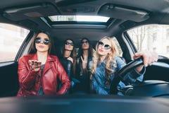 De groep vrienden die pret hebben wet aandrijving de auto Het zingen en het lachen op de weg royalty-vrije stock fotografie