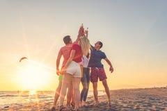 De groep vrienden geniet van op het strand stock afbeeldingen