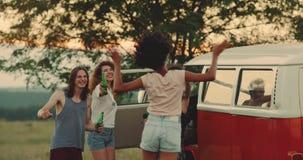 De groep vrienden heeft picknicktijd met hun retro bestelwagen in het midden van gebied het drinken bier die en een goed glimlach stock video