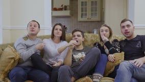 De groep vrienden let thuis op film en eet popcorn stock video
