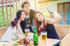 De groep vrienden neemt selfie en etend voedsel zijn gelukkige enj stock afbeelding