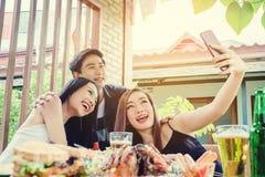 De groep vrienden neemt selfie en etend voedsel zijn gelukkige enj royalty-vrije stock afbeelding