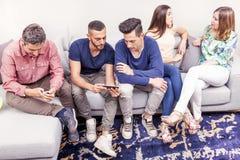 De groep vrienden op de laag die en bekijkt de telefoon spreken stock foto