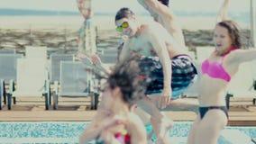De groep vrienden springt in de pool Plonsen van water stock videobeelden
