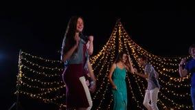 De groep vriendenrust in de avond het bedrijf danst en heeft pret op het stadium stock footage
