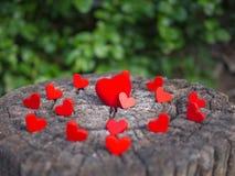 De groepsharten op de houten vloer worden geplaatst en hebben exemplaarruimte voor ontwerp in uw werk dat De rode harten vervoere stock foto's