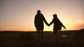 De de groepswerkmoeder en dochter op vakantiereis met een rugzak, heffen omhoog hun handen op bewonder het landschap vanaf bovenk stock video