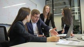 De groepswerknemers spreken terwijl het zitten in modern bureau stock footage