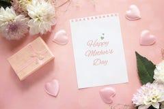 De groetbericht van de moedersdag met dahlia's en giftvakje op een roze stock fotografie