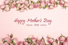 De groetbericht van de moedersdag met kleine droge rozen op roze backgr royalty-vrije stock afbeeldingen