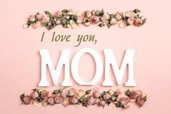 De groetbericht van de moedersdag met kleine droge rozen op roze backgr stock afbeelding