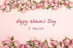 De groetbericht van de vrouwen` s Dag met kleine droge rozen op roze backgr stock afbeeldingen