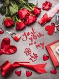 De groetkaart van de valentijnskaartendag met liefdesymbolen, rode decoratie en rozen en met de hand geschreven van letters voorz Stock Afbeeldingen