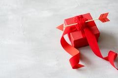 De groetkaart van de valentijnskaartendag, model met exemplaarruimte Rode giftdoos met draadhart, Cupid& x27; s pijl, linten op g stock afbeeldingen