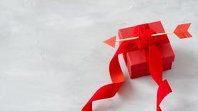 De groetkaart van de valentijnskaartendag, model met exemplaarruimte Rode giftdoos met draadhart, Cupid& x27; s pijl, linten op g royalty-vrije stock foto's