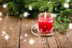 De groetkaart voor de Kerstmis en Nieuwjaarvakantie dirkt Lichten van de achtergrond takken Rode Kaars Houten Kerstmis als achter Royalty-vrije Stock Foto's