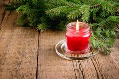De groetkaart voor de Kerstmis en Nieuwjaarvakantie dirkt Lichten van de achtergrond takken Rode Kaars Houten Kerstmis als achter Royalty-vrije Stock Afbeeldingen