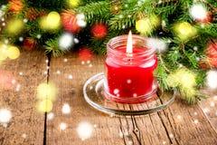 De groetkaart voor de Kerstmis en Nieuwjaarvakantie dirkt Lichten van de achtergrond takken Rode Kaars Houten Kerstmis als achter Royalty-vrije Stock Fotografie