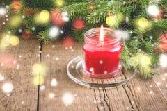De groetkaart voor de Kerstmis en Nieuwjaarvakantie dirkt Lichten van de achtergrond takken Rode Kaars Houten Kerstmis als achter Royalty-vrije Stock Afbeelding