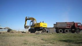 De grond van de graafwerktuiglading van bouwwerf van de Arena van stadionvolgograd in een kipwagenvrachtwagen stock videobeelden