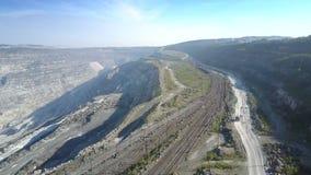 De grondweg van satellietbeeldspoorwegen bij asbestkuil door heuvels stock footage