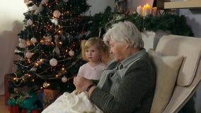 De grootmoeder breit een sok terwijl het zitten als voorzitter stock footage