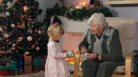 De grootmoeder breit terwijl het zitten als voorzitter stock videobeelden