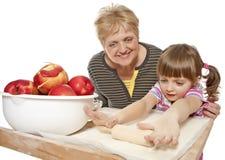 de grootmoeder die haar kleindochter onderwijst bakt stock afbeeldingen