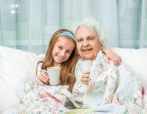 De grootmoeder en de kleindochter drinken thee Stock Afbeelding