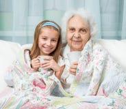 De grootmoeder en de kleindochter drinken thee Stock Fotografie